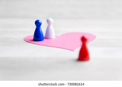 Love triangle or being third wheel. Having affair, infidelity or cheating concept. Board game pawns and paper heart on table.