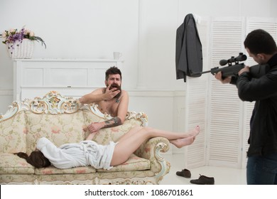 Love triangle concept. Husband arrived home to see wife cheat with lover. Aggressive man with gun to shoot couple in love. Hipster shocked to see gunman in bedroom. Cheating, jealousy and violence.
