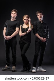 Love triangle. Young woman posing with two young man on a dark background in studio