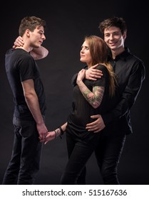 Love triangle. Young woman posing with two young man on a dark background