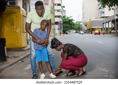 Love and trust as family values. Mother and father with son outdoors. Summer vacation of happy family. Mother tired of her son's shoes