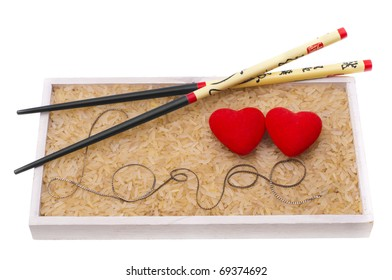 love, two red hearts in rice and two chopsticks