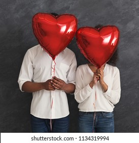 Love and Valentines day. African-american couple hiding faces behind red heart shaped balloons, black studio background