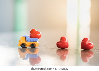 Love and Valentine's day Concept. Mini truck carry plastic red hearts on ground