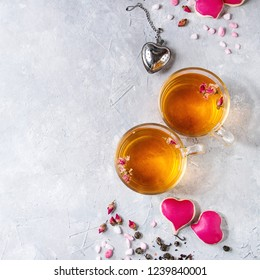 Love Valentines day greeting card with two glasses of hot tea, rose buds, heart shape homemade cookies as gift, pink sugar, tea strainer over gray texture background. Top view, space. Square image
