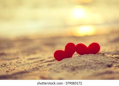 Liebe zum Valentinstag - rote Herzen am Seil hängen zusammen mit Sonnenuntergang-Silhouette