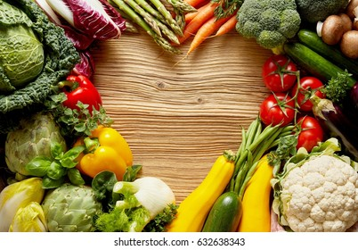 Love for vegetables background concept, with lots of fresh organic food forming heart-shaped gap in the middle, placed on wooden table