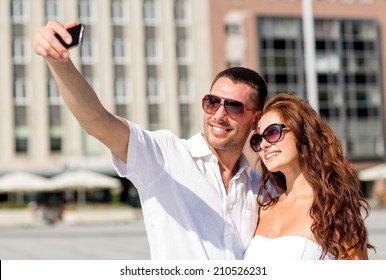 love, wedding, summer, dating and people concept - smiling couple wearing sunglasses making selfie with smartphone in city