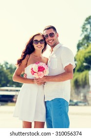 love, wedding, summer, dating and people concept - smiling couple wearing sunglasses standing with bunch of flowers in city