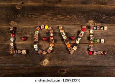 LOVE word arranged with pralines on the wooden plank background