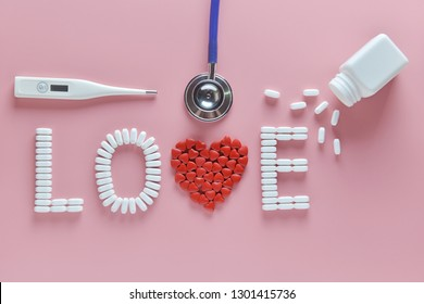 """""""LOVE"""" word made from medicine pills, red heart shape pouring out of white bottle and stethoscope, temperature, on pink background. Concept of Valentine's Day or pharmacy, Medical."""