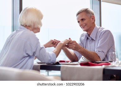 Love words. Pleasant merry mature man smiling while staring at wife and holding her hands