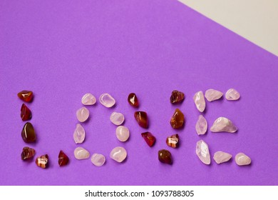 Love - written with colored stones on violet background
