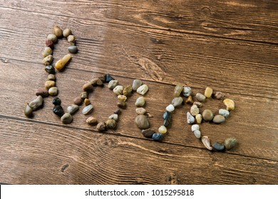 Love written with stones on a wooden background