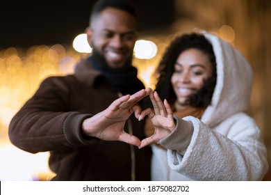 I Love You. Closeup of cheerful positive african american couple making heart shape with fingers walking together in the evening, looking at hands, selective focus, blurred background. Valentine's day
