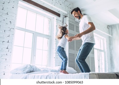 I love you, dad! Handsome young man at home with his little cute girl are having fun and jumping on bed. Happy Father's Day!