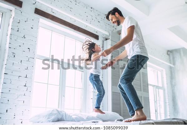 愛してるわパパ!家にいるハンサムな若い男性が、かわいい女の子と楽しみ、ベッドで飛び跳ねている。父の日おめでとう!