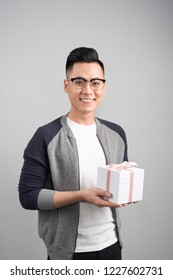 With love for you. Good looking young man holding a gift box and looking at camera while standing against grey background.