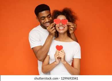 I love you. Happy young man is covering female eyes with surprise and giving her heart cards, orange studio background