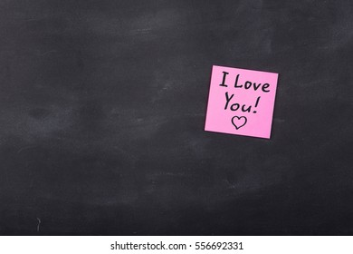 I love you inscription on colorful stickers on blackboard