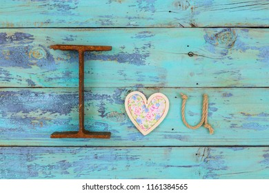 I Love You in iron, floral wood heart and U shaped rope hanging on antique teal blue rustic wooden background; symbolic love concept made with different texture materials