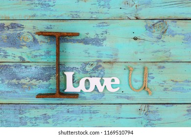 I Love You in iron, white wood word Love and U shaped rope hanging on antique teal blue rustic wooden background; symbolic love concept made with different texture materials