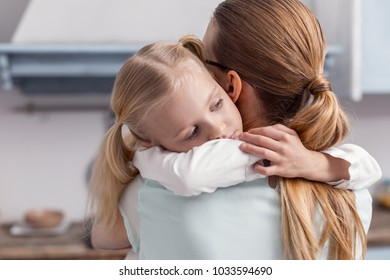 I love you. Kind beautiful little girl hugging mother while looking aside and wearing ponytails