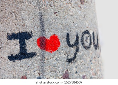 I love you lettering with a bright red heart on a gray rough concrete surface