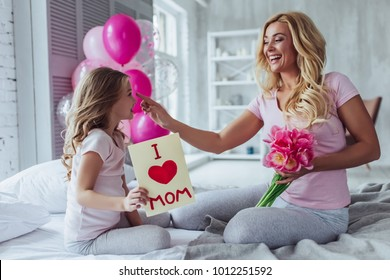 I love you, mom! Attractive young woman with little cute girl are sitting on bed and spending time together at home. Mom is receiving presents from daughter on Mother's Day. Happy family concept.