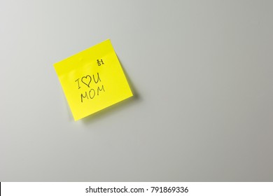 i love you mom note on yellow paper sticker on a white fridge close-up