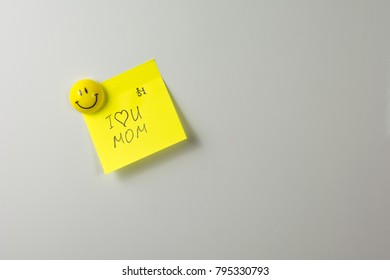 i love you mom note on yellow paper sticker smiling magnet on a white fridge close-up