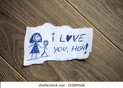 I love you, mom written on piece of paper, on a wood background