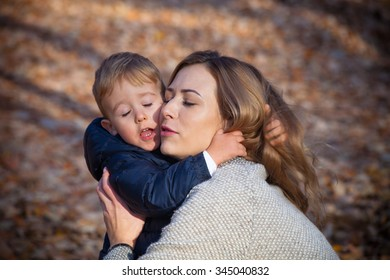 I love you mom, young mother with her little  son in hug, autumn day in park, closeup