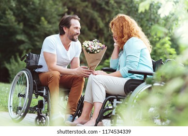 Love you to the moon and back. Cheerful disabled man smiling while looking at his soulmate and surprising her with flowers during their date outdoors.