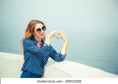 Love you. Portrait close up happy smiling young woman showing heart sign gesture with hands isolated sea, seascape blue sky background. Positive human emotion expression feeling attitude body language