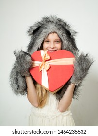 i love you. Small girl wear winter hat scarf. Winter fashion trends for kids. valentines day. present box in shape of heart. red heart. love. boxing day. valentines day shopping. present with love.