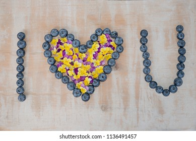 i love you text, formed with big blueberries and horned violet blossoms on wooden background