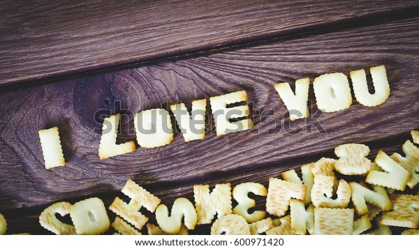 I love you. Text from the salty crackers as printed English letters that lie on a wooden background. Top view.