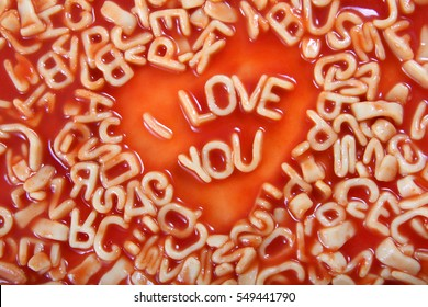i Love you text written in Alphabetti Spaghetti pasta shaped letters in a heart shape, with tomato sauce around it.