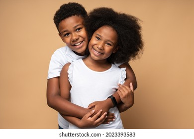 I love you. Waist up portrait view of the lovely multiracial boy embracing with tenderness his curly sister and looking at the camera. Family relationships concept