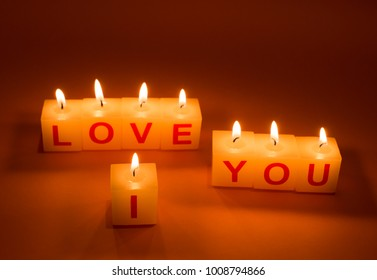 I Love You words on candle. Lights on pink background