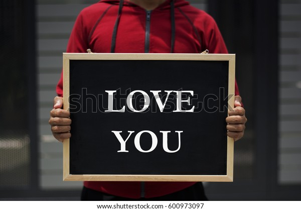 love you written on blackboard with someone is holding it