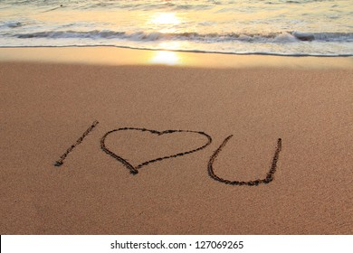 I love you written in the sand on the beach at sunset.