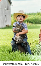 Love your cat day. Love Your Pet Day. Random Acts of Kindness Week. Little boy with a cowboy hat holding a cat outdoors.