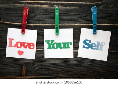 Love your self in squre paper notes hanging by clothespin on wood