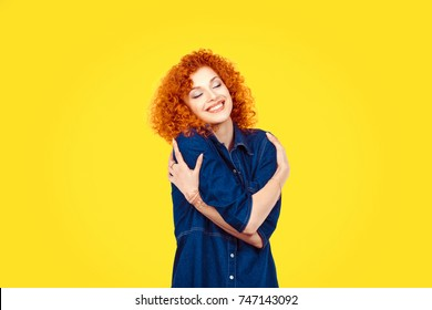 Love yourself concept. Closeup portrait confident smiling woman holding hugging herself isolated yellow wall background. Positive human emotion, facial expression feeling reaction situation attitude