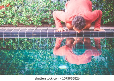 Love yourself / young indian man kissing his shadow in blue water pool on his vacation
