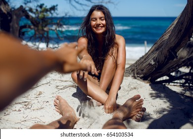 A loved make touches his girlfriend's. Love in the air concept, funny times, affair on the beach of the Corsica island, France seascape background. Horizontal view.