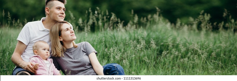 Love,family, happiness, lifestyle, parenthood and togetherness. Outdoor portrait of dreamy mother, father and little daughter sitting at grass together relaxing in nature