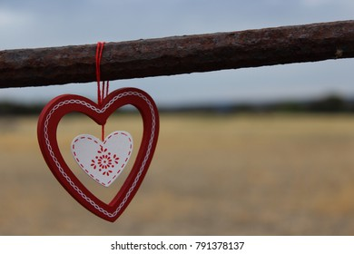 Loveheart hanging from rusty gate and blue sky, yellow grass background.